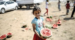 """TOPSHOTS A Syrian girl holds a water mellon near the Akcakale crossing gate between Turkey and Syria at Akcakale in Sanliurfa province on June 16, 2015. Turkey said it was taking measures to limit the flow of Syrian refugees onto its territory after an influx of thousands more over the last days due to fighting between Kurds and jihadists. Under an """"open-door"""" policy, Turkey has taken in 1.8 million Syrian refugees since the conflict in Syria erupted in 2011. AFP PHOTO / BULENT KILIC"""
