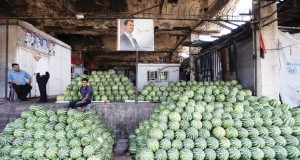 Syrian traders sit next to a portrait of President Bashar al-Assad at a fruit and vegetable market in central Damascus on September 21, 2015. AFP PHOTO / JOSEPH EID